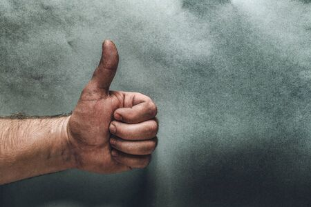Closeup of male hand showing thumbs up sign. blue background. toned image. art Stok Fotoğraf