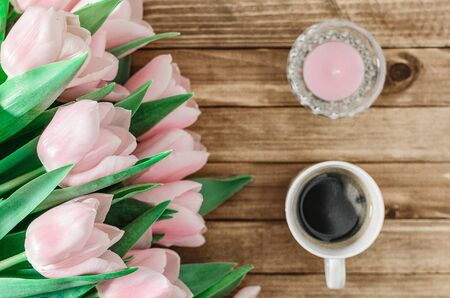 Background with bouquet of pink tulips on brown wooden boards with cup of coffee and candle. Copy space. Top view. Toned image. Horizontal