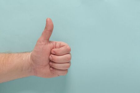 Closeup of male hand showing thumbs up sign against blue background