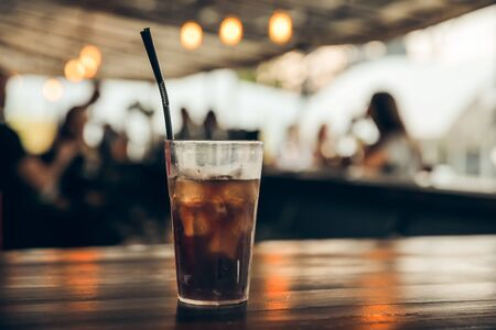 glass of cola with ice on a wooden table at an outdoor summer cafe. peoples on background 스톡 콘텐츠