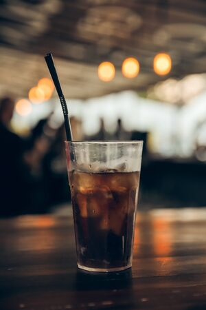 glass of cola with ice on a wooden table at an outdoor summer cafe. peoples on background. vertical