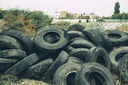 many old tires stacked on the grass in city. Broken tire damaged, A bunch of old tires from used cars. Environmental pollution. Dump tires Stok Fotoğraf