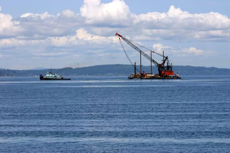 Tow ship is towing barge crane near Alki Beach, Seattle Imagens