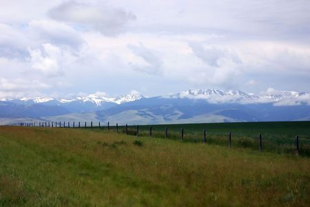 View of Tetons peaking through the farmlands on the way to Yellowstone national park Imagens