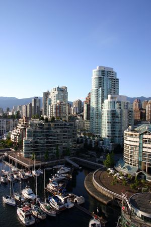Apartment complexes with boats and pier by False Creek in Vancouver, Canada