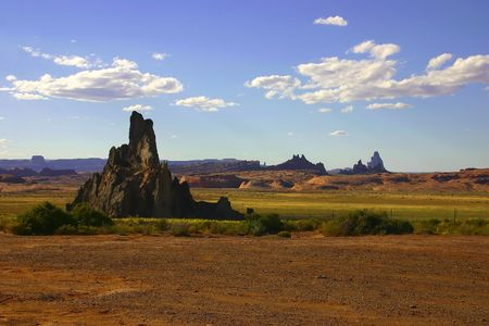 Shiprock monument in New Mexico on a clear day with blue cloudy skies and other rocks in the background Imagens