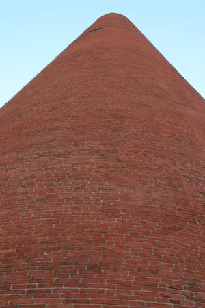 Red Brick Shot tower towering in Baltimore, Maryland, near Little Italy