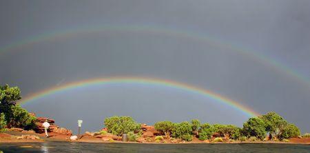 Man runs towards rainbows in Dead Horse park in Utah Canyonlands Imagens