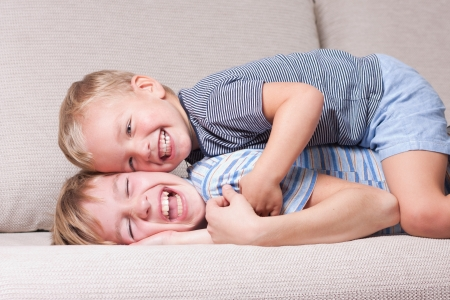 Two brothers laugh, indoor photo