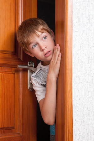 Surprised boy peeks from behind  door  indoor photo
