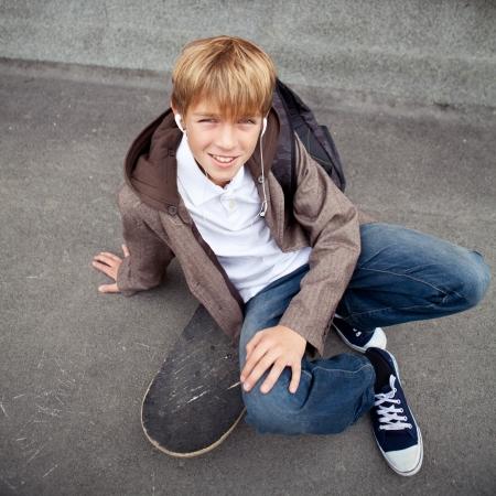 School teen sits on skateboard near school, day