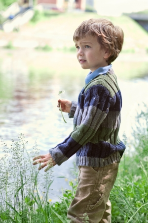 Elegant boy stands on  banks of River, summer photo