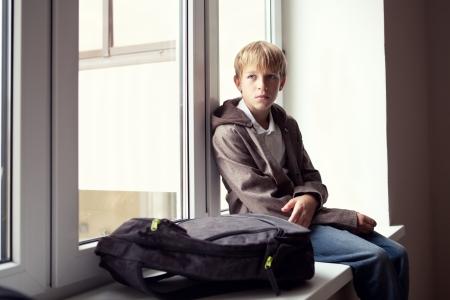 Schüler sitzt an einem Fenster im Freien