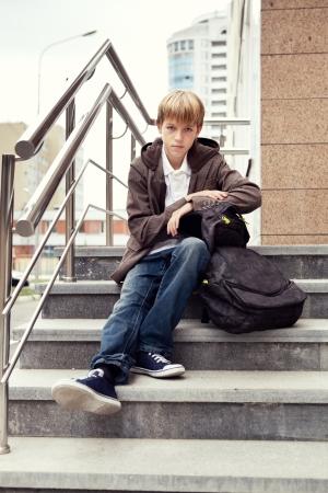 Serious teen sitting on stairs. outdoor Standard-Bild