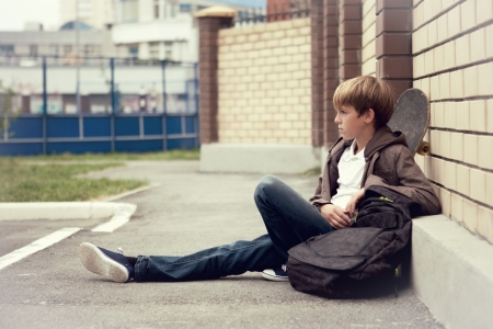 School teen with schollbag and skateboard, day 免版税图像