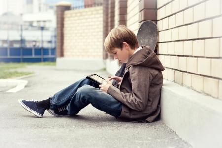 School boy with electronic tablet sitting, 免版税图像