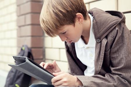 ni�o con mochila: Escuela muchacho sentado con tableta electr�nica,