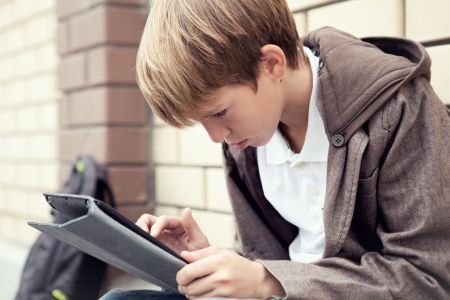 School boy with electronic tablet sitting, photo