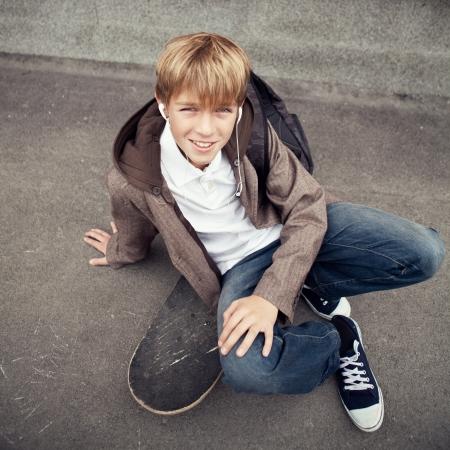 ni�o con mochila: School adolescente se sienta en el monopat�n cerca de la escuela, el d�a Foto de archivo