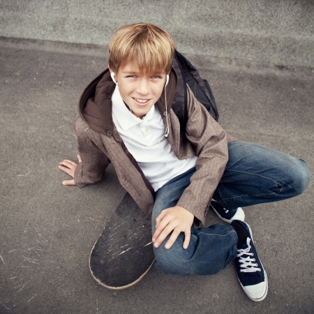School teen sits on skateboard near school, day photo