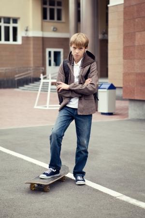 Schule Teenager mit Schultasche und Skateboard, Tag