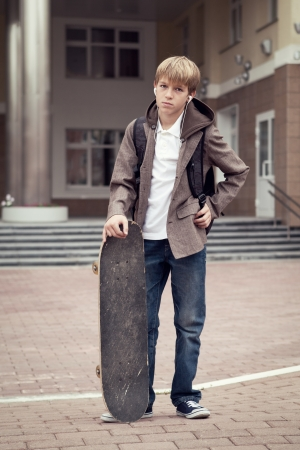 School teen with schoolbag and skateboard, day photo