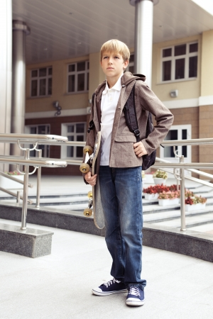 School teen with schollbag and skateboard, day photo