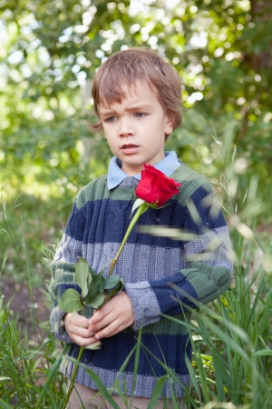 Sad boy holding red rose in her hand,  park photo