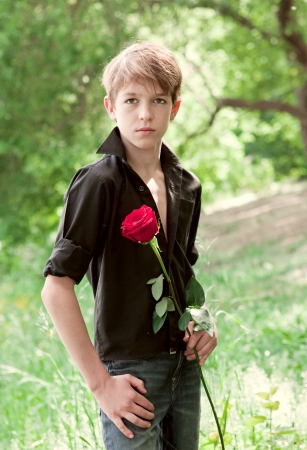 A teenager with a rose in hand, park photo