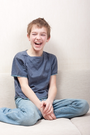 Frohe Teenager sitzt auf der Couch und lacht Lizenzfreie Bilder