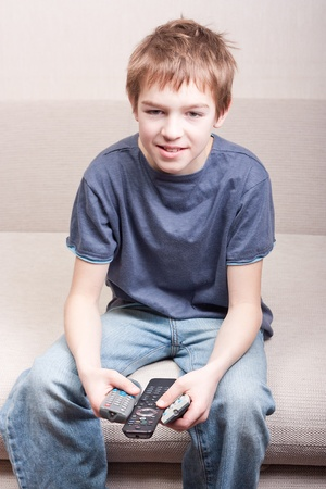 Teen watches television and holds three remote in room photo