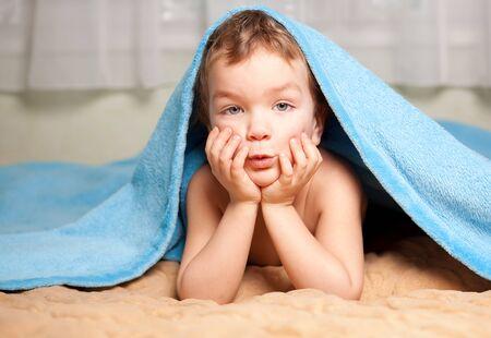 counterpane: Small boy under a blue blanket Stock Photo