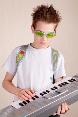 Teen plays on synthesizer, indoor Stock Photo