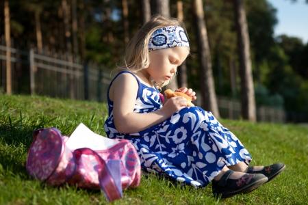 Beautiful girl eating bun is on green grass