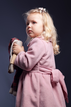 Portrait of  girl in pink coat on  black background Stock Photo - 15067489