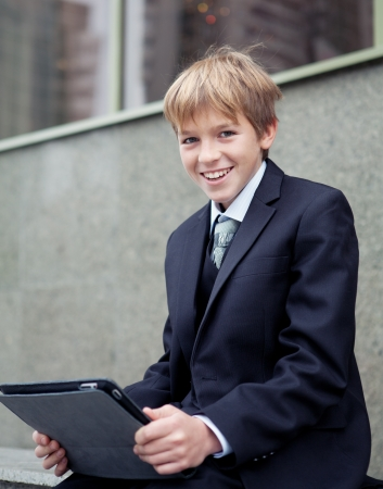 School boy with electronic tablet sitting,outdoor photo
