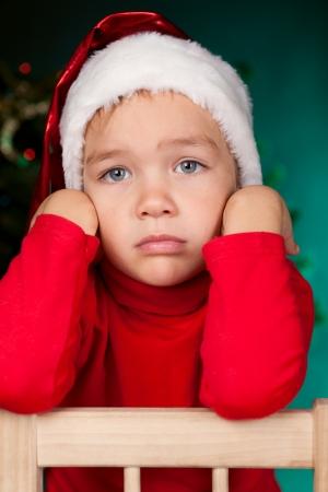 sad boy: Small child in santa hat