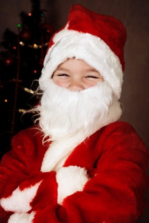 Cheerful boy in Santa Claus suit, new year photo