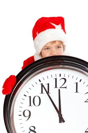 Boy in cap of Santa Claus and large clock, isolation, studio photo