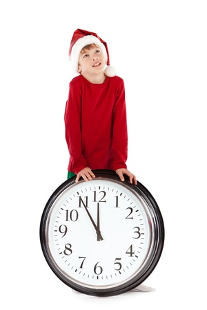 dreamy eyed: Boy in cap of Santa Claus and large clock, isolation, studio