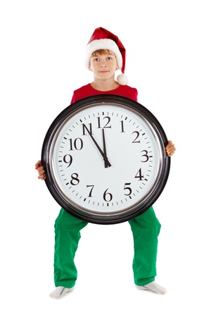 Boy in cap of Santa Claus and large clock, isolation, studio Stock Photo - 16143974