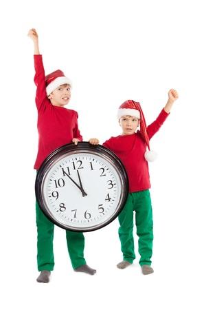 Boys in cap of Santa Claus and large clock, isolation, studio photo