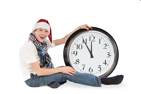 Teenager in cap of Santa Claus and large clock, isolation, studio Stock Photo - 16276331