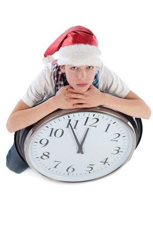 Teenager in cap of Santa Claus and large clock, isolation, studio photo