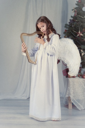 Thoughtful nice girl with wings, christmas photo