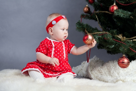baby christmas: Little girl in red dress sitting near Christmas tree, indoor