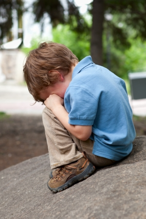 sad boy: Small child sits on stone in park Stock Photo