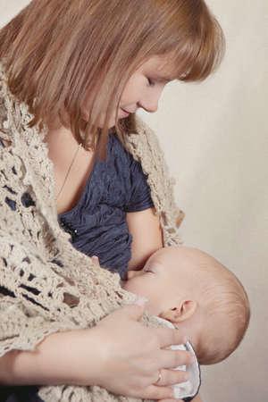 Woman breast feeding baby, indoor photo