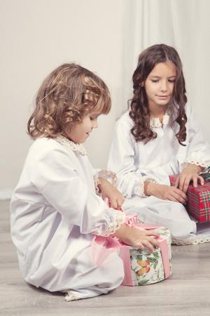 baby open present: Girls watching Christmas gifts, indoor Stock Photo