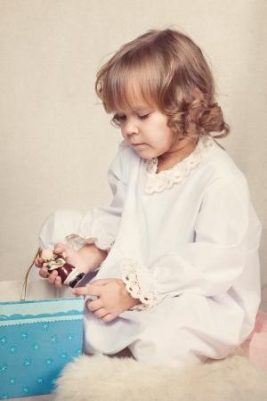baby open present: Girl watching Christmas gifts, indoor